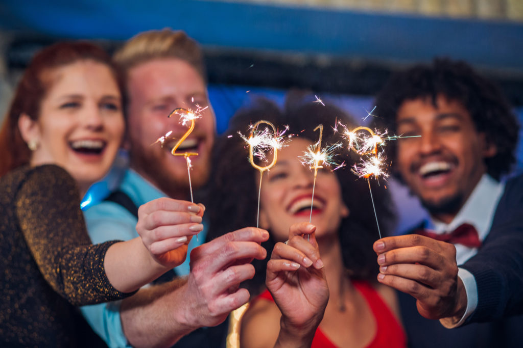 Joyful young people holding sparklers in a club